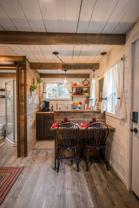 The kitchen and breakfast bar (dining space) can be visibly seen here, along with the wooden beams on show in the ceiling.