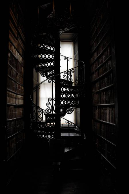A spiral staircase inside a narrow corridor, with a black arty effect to the photo.
