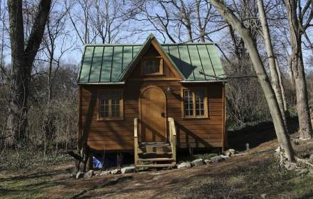 Front view of the Nashville Wonderland tiny home, in its forest surroundings.