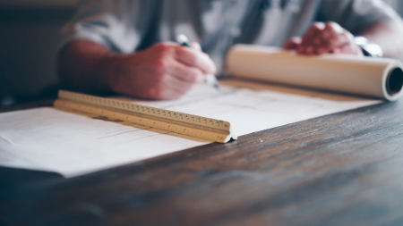 Out of focus picture of architect with long ruler and a roll of paper, from Daniel McCullough of Unsplash.