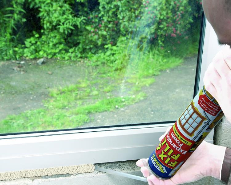 Expanding foam being used to fill a gap below the window cil frame, from Amazon.co.uk.