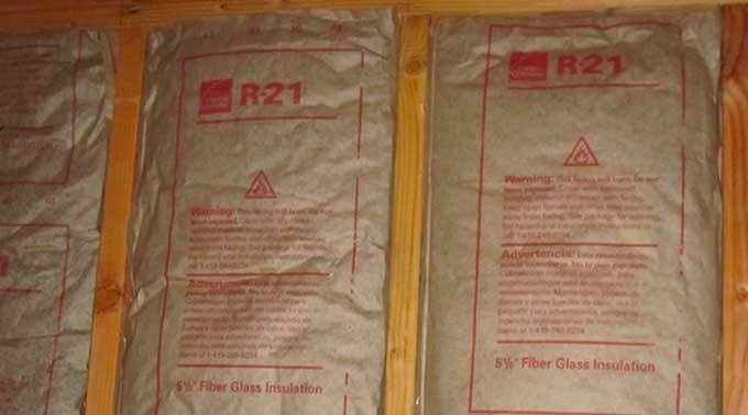 Thick 5.5 inch R-21 fibreglass roll insulation in-between the vertical wood studs, from Less Everything.