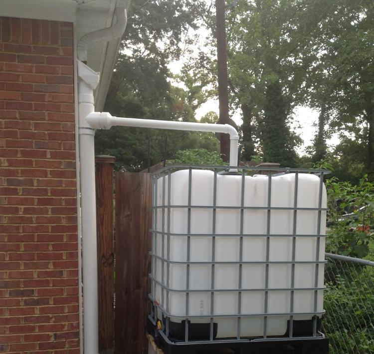 Rainwater collection via a big water container which has a pipe running to it from the guttering, from SunRainEarth blog.