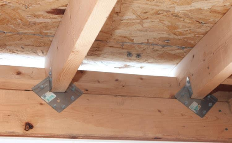 Hurricane brackets/ties applied to the roof joists and the wall timber, from Plasticine House.