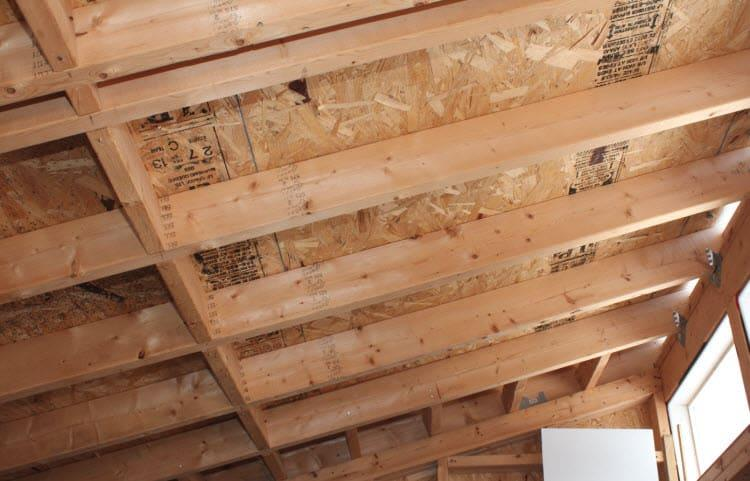 An internal look at the underside of a roof that has had sheathing attached to the top of the roof, from Plasticine House.