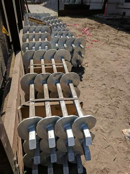 A range of shorter depth screw piles in a building yard, waiting to be shipped out, from Wikipedia