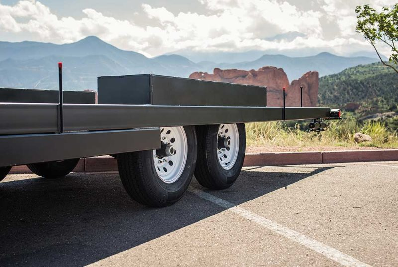 Tumbleweed's tiny house trailer with frame on top of big wheels and mountain terrain in the background, from Tumbleweed's website.