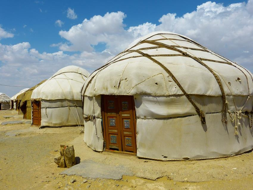A row of yurts in a desert type area, from LoggaWiggler of Pixabay.